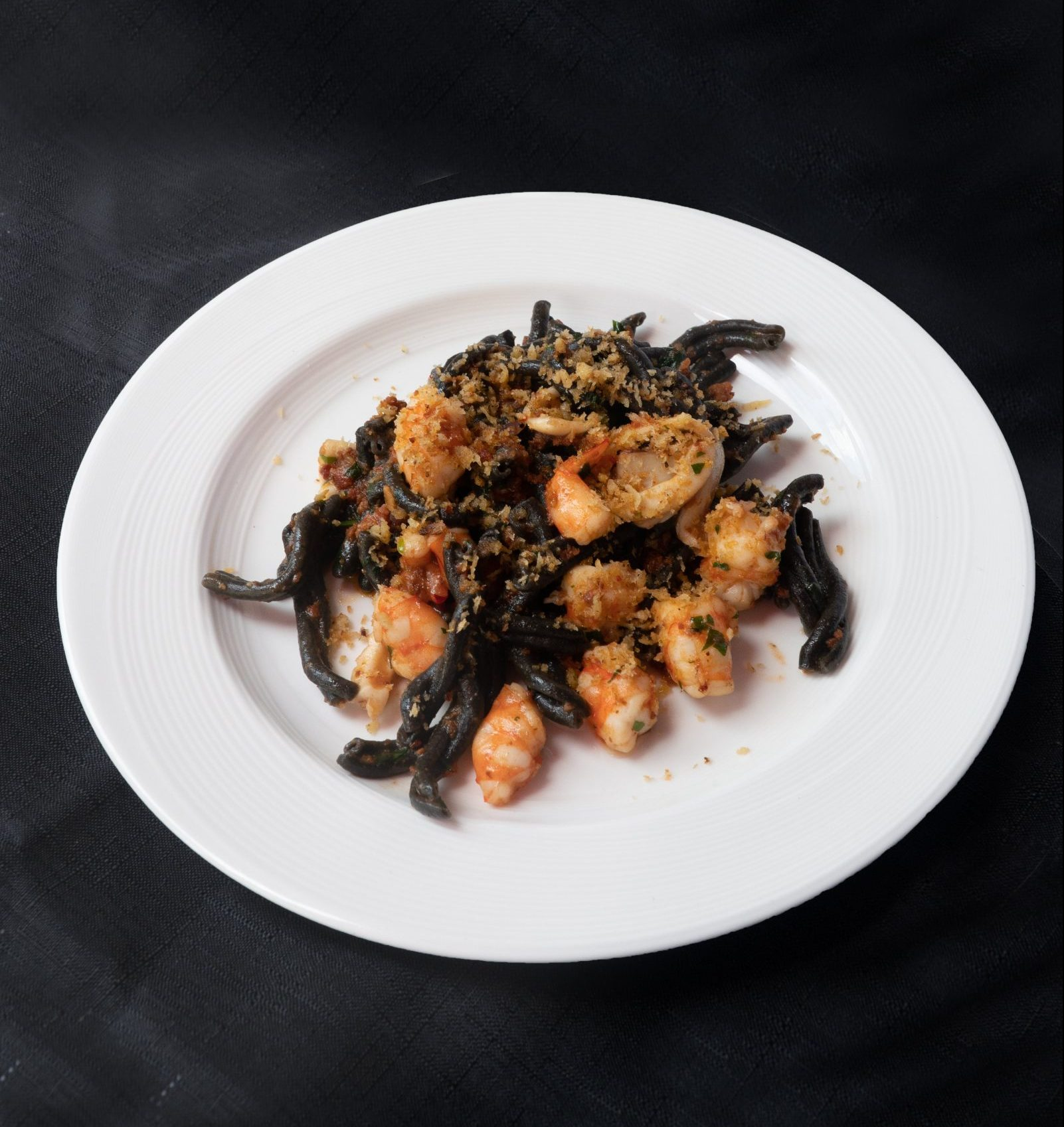 Squid ink casarecce, 'nduja, squid, fresh prawn, and toasted crumbs