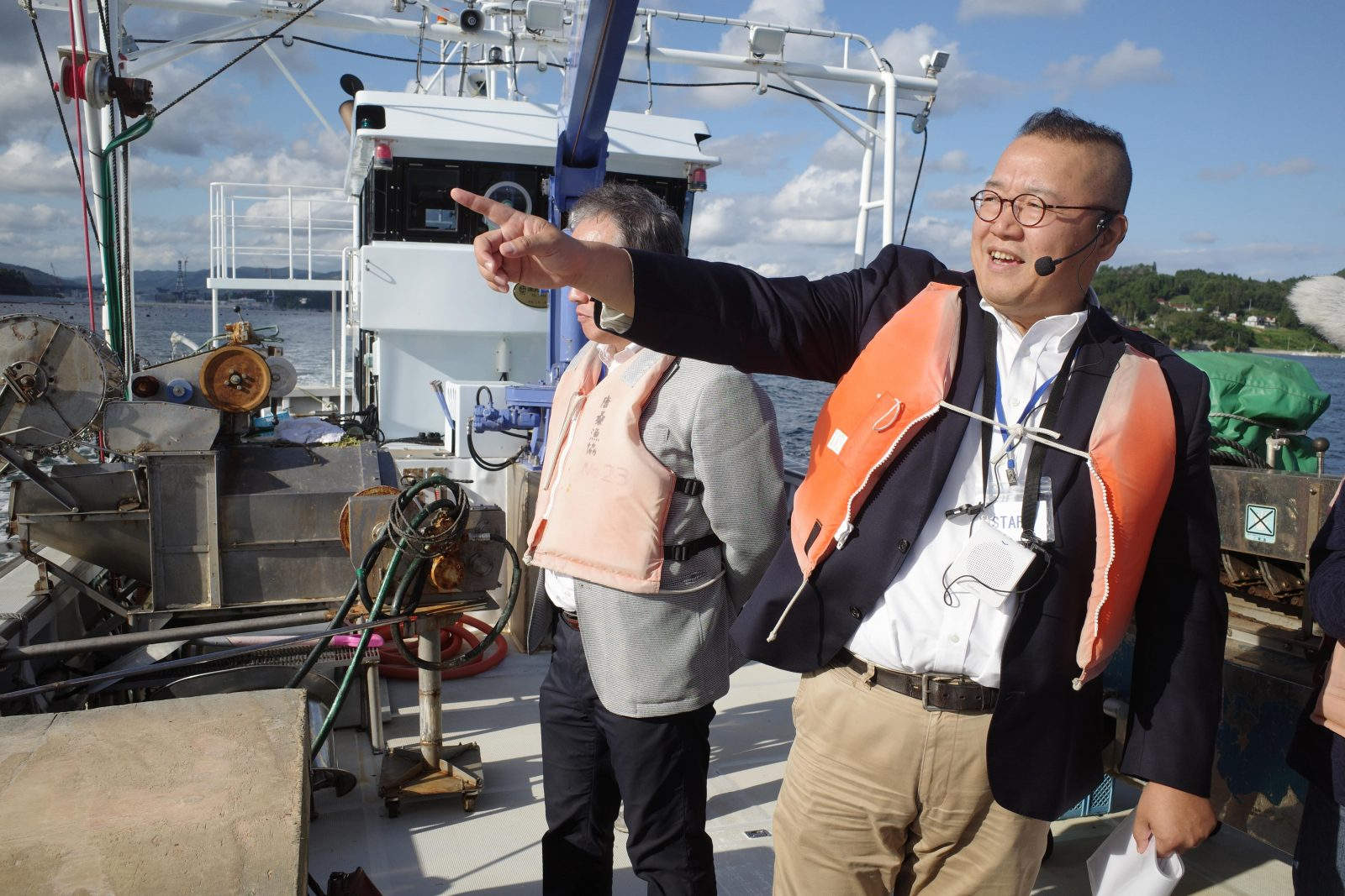 Cafe owner Yasutada Onodera showing visitors around Kesennuma